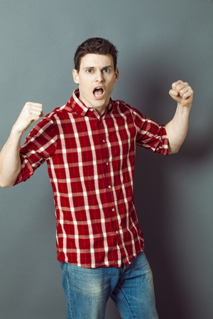 exasperation: muscle concept - shouting young man with arms raised expressing his exasperation and frustration,studio shot,low contrast effect