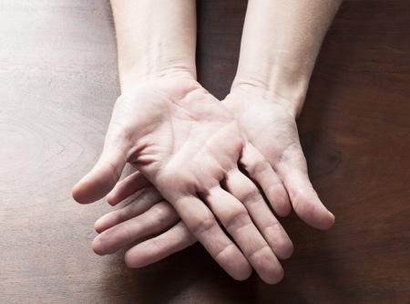 generosidad: hablando manos concepto - vacías manos femeninas que piden caridad o generosidad en mesa de madera, tiro del estudio Foto de archivo