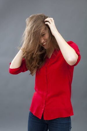 haircare concept - cheerful attractive young woman scratching her hair for beauty excitement,studio shot