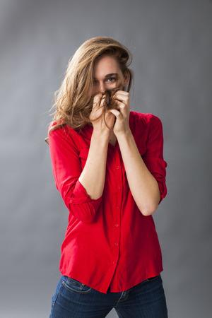mouth: concepto de protecci�n - mujer joven adorable que juega con su pelo para cubrir su boca para la timidez y confusi�n, tiro del estudio