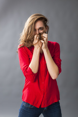 long hair: protection concept - adorable young woman playing with her hair to cover her mouth for shyness and confusion,studio shot