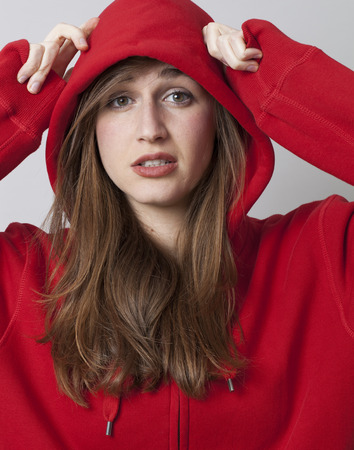 head protection: protection concept - beautiful streetwear young woman covering her head with red hoodie for self-protection,studio shot