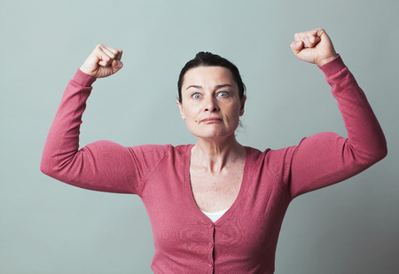 emphasized: muscle concept - stunned 40s woman gesturing with arms raised showing her emphasized strength and independence,studio shot,low contrast effect