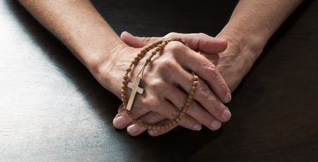 confession: talking hands concept - female hands holding tight a Christian cross praying for confession on dark wooden table,studio shot