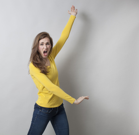 hair problem: excitement and frustration concept - unhappy young woman showing a high and low choice,displaying empty hands for unequal comparison,studio shot