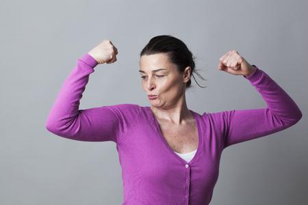 autonomia: concepto del músculo - mujer juguetona hermosas 40s orgullosos de mostrar sus músculos para el símbolo de la autonomía y la libertad, tiro del estudio Foto de archivo