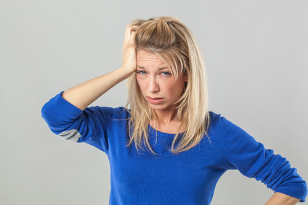 hangover or insomnia concept - sick young blond woman with bags scratching her hair for headache,studio shot Stock Photo