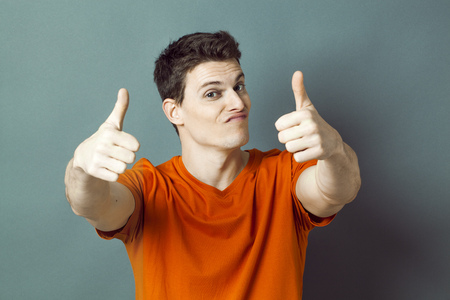 dubious: optimism concept - dubious 20s athletic man with orange t-shirt and thumbs up for ok or success, studio grey background, green effects