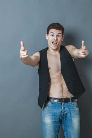 bare chest: optimism concept - smiling 20s sportsman with bare chest and fingers pointing to camera expressing excitement, studio grey background