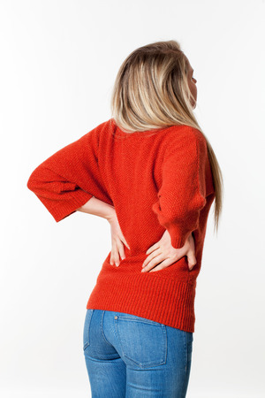 backache, lumbago, scoliosis health problems - young blond woman suffering from back pain, touching her lower vertebrae,white background Stock Photo