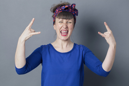 rebellion: optimism concept - stylish 30s woman shouting with hard rock hand gesture for rebellion or bold success, studio grey background Stock Photo
