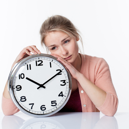 career timing: time concept - sad beautiful young blond woman leaning on a clock, showing depressing nostalgia of adolescence, white background Stock Photo