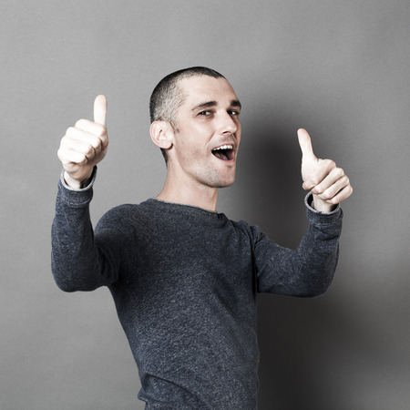 arrogancia: optimism concept - excited 30s man with short hair and thumbs up for congratulation or success, studio grey background, texture effects Foto de archivo