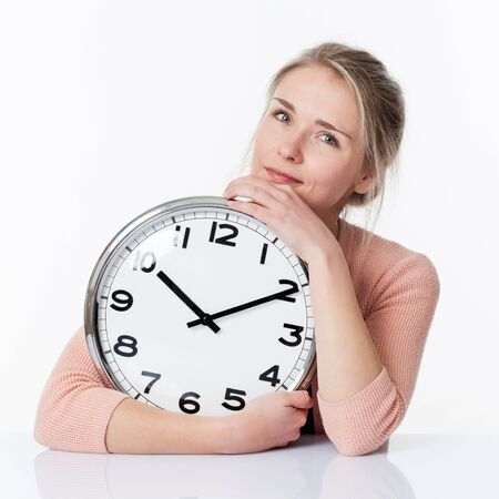 career timing: time concept - serene beautiful young blond woman embracing a clock,smiling for enjoying a relaxing time, white background