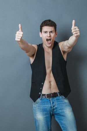 nackte brust: Konzept Optimismus - begeistert 20s Sportler mit nackten Brust und den Daumen nach oben schreien zu genehmigen oder zu feiern, Studio grauen Hintergrund