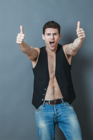 bare chest: optimism concept - thrilled 20s sportsman with bare chest and thumbs up shouting to approve or celebrate, studio grey background Stock Photo