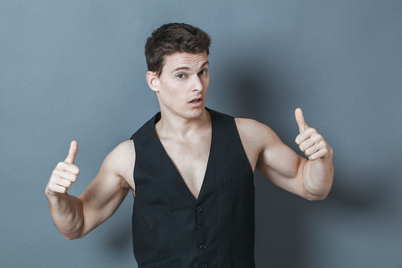 20s: optimism concept - arrogant 20s sporty man with bare chest showing his muscles, studio grey background Stock Photo