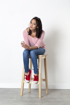 bothered: relaxation on the phone - unhappy young multi-ethnic female student dialing on her mobile phone, sitting on a stool to enjoy communication, white background Stock Photo