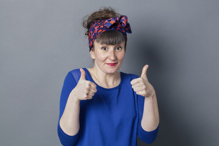 embarrassed: optimism concept - shy retro 30s woman smiling with two thumbs up for embarrassed success, studio grey background
