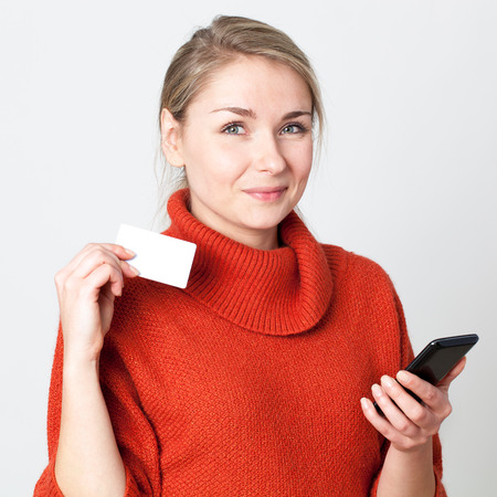 mobile commerce: mobile commerce - happy young blond woman consuming on cell phone with copy space credit card for modern convenience, white background