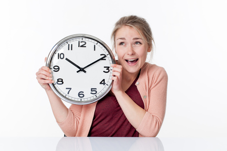 impatience: time concept - thrilled beautiful young blond woman holding a clock with impatience and imagination, white background