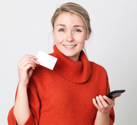 mobile commerce: mobile commerce - thrilled young blond woman making a shopping transaction online with copy space credit card for modern convenience, white background