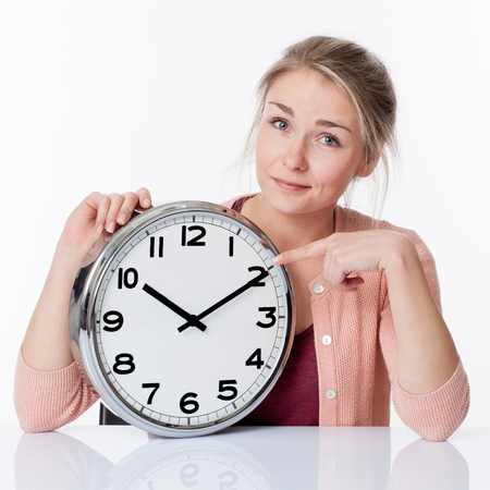 career timing: time concept - smiling beautiful young blond woman pointing to a clock, showing patience and relaxed management of deadlines, white background