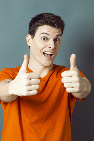 extrovert: optimism concept - thrilled 20s athletic man with orange t-shirt and thumbs up for ok or success, studio grey background, green effects Stock Photo
