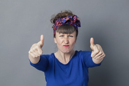 enraged: optimism concept - enraged 30s woman frowning with two thumbs up in the foreground for fighting success, studio grey background