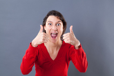 extrovert: optimism concept - ecstatic beautiful young woman shouting with two thumbs up for excitement and success, studio grey background Stock Photo