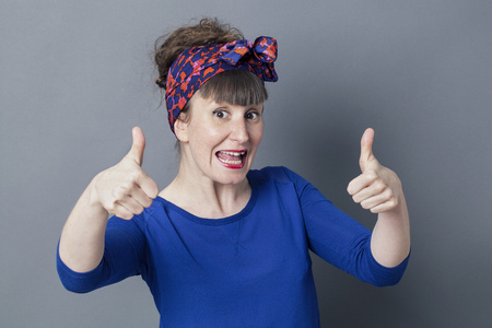 two thumbs up: optimism concept - excited retro 30s woman laughing with two thumbs up for cool success, studio grey background