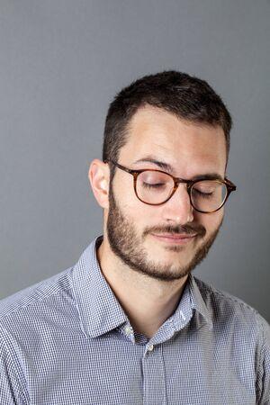 concept de fatigue d'entreprise - dormir jeune homme avec une barbe et des lunettes debout avec les yeux fermés, se détendre à faire une sieste, studio shot