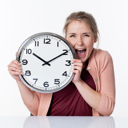 impatience: time concept - ecstatic beautiful young blond woman holding a clock,laughing for fun and impatience, white background Stock Photo