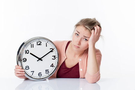 career timing: time concept - bored beautiful young blond woman showing a clock disillusioned and annoyed by schedule, white background