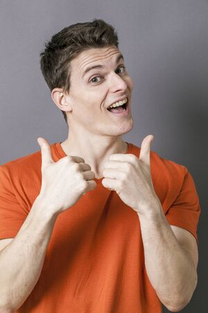 20s: optimism concept - excited 20s athletic man with orange t-shirt and thumbs up for sporty dynamism, studio grey background Stock Photo
