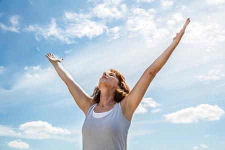 buiten ademen - zen vrouw van middelbare leeftijd die yoga opzoekt en haar armen omhoog houdt, meditatie beoefend voor vrijheid over de zomer blauwe lucht, lage kijkhoek