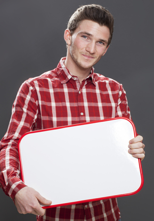 shyness: panel announcement - shy young male student  smiling in holding a copy space board as teaser, gray background