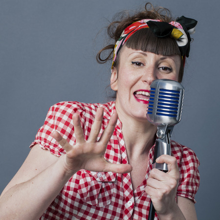 30s: fifties singer in studio - 30s female performing artist with retro style singing in old fashioned microphone, closeup over gray background