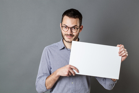 teaser: panel announcement - happy young man with eyeglasses and beard holding a blank banner for marketing, gray background Stock Photo