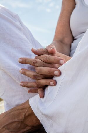 low angle view: spirituality outdoors - closeup of praying hands of a yoga woman meditating in lotus position, wearing white,low angle view