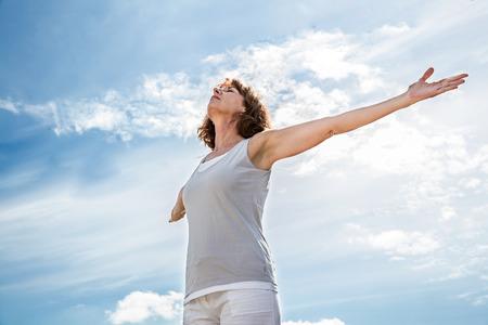 respirazione fuori - zen donna di mezza età di yoga aprendo il suo chakra con le braccia alzate, la pratica della meditazione per la libertà nel cielo azzurro d'estate, Inquadratura dal basso