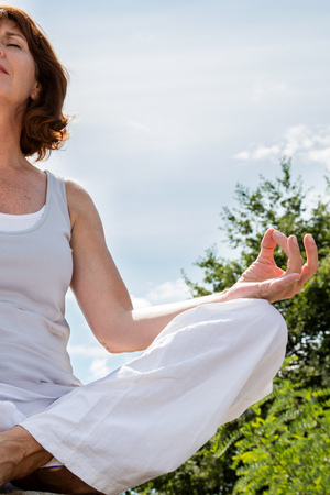 inner peace: breathing outside - closeup of a 50s yoga woman sitting in lotus position, seeking for inner peace with green background,low angle view