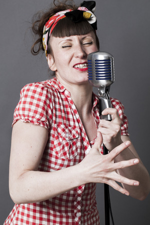 fifties: fifties singer in studio - young woman with retro style singing in old fashioned microphone, gray background