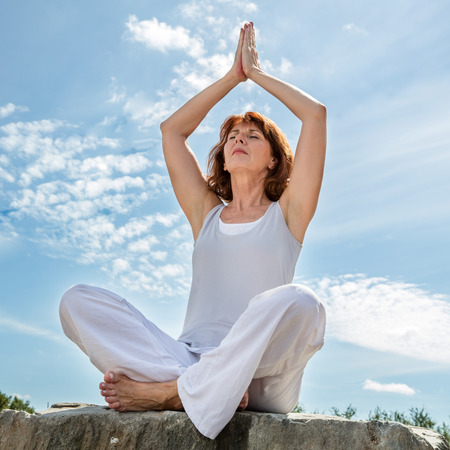 exercising outdoors - beautiful middle aged woman praying in yoga position, closing eyes for balance over summer blue sky,low angle view