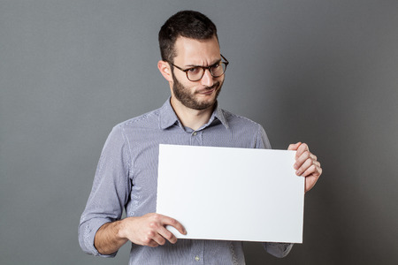 panel announcement - displeased young man with beard and eyeglasses claiming on a blank banner for copy space text, gray background
