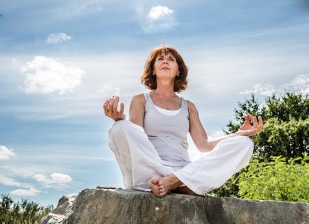 respiracion: respirar aire libre - hermosas 50s mujer sentada en una piedra en posición de loto de yoga, en busca de la espiritualidad sobre el cielo de verano azul, ángulo de visión baja