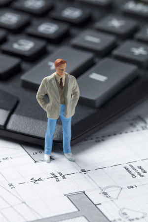 draftsman: concept of home owner in housing market with miniature investor or entrepreneur on calculator Stock Photo
