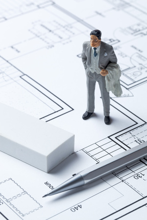 housing market: real estate businessman miniature with eraser and pencil on architect blueprint for concept of housing market Stock Photo