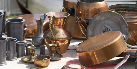 bric: old copper carafes and pans displayed for sale at second hand shop