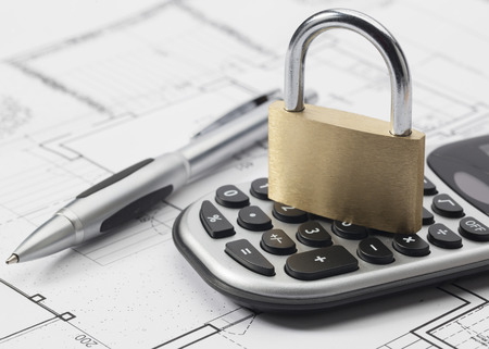 lock: padlock and calculator on new building blueprint Stock Photo